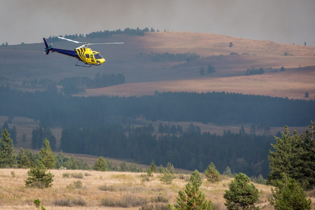 A helicopter flies south of Anarchist Mountain as planes and helicopters attack a fire approaching from the U.S. (Richard McGuire photo)