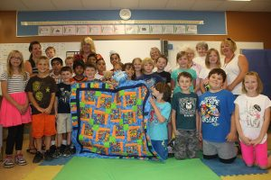 Photo by Keith Lacey Heather Langley's (back row third from left) Grade 3 class at Osoyoos Elementary School wrapped up its Roots of Empathy program last week with members of the Osoyoos Quilters Guild handing out cake and presenting a quilt to the class. Young mother Randee Ebe (back row left) and her 10-month-old son Jaxon made nine visits during the school year to Langley's classroom.