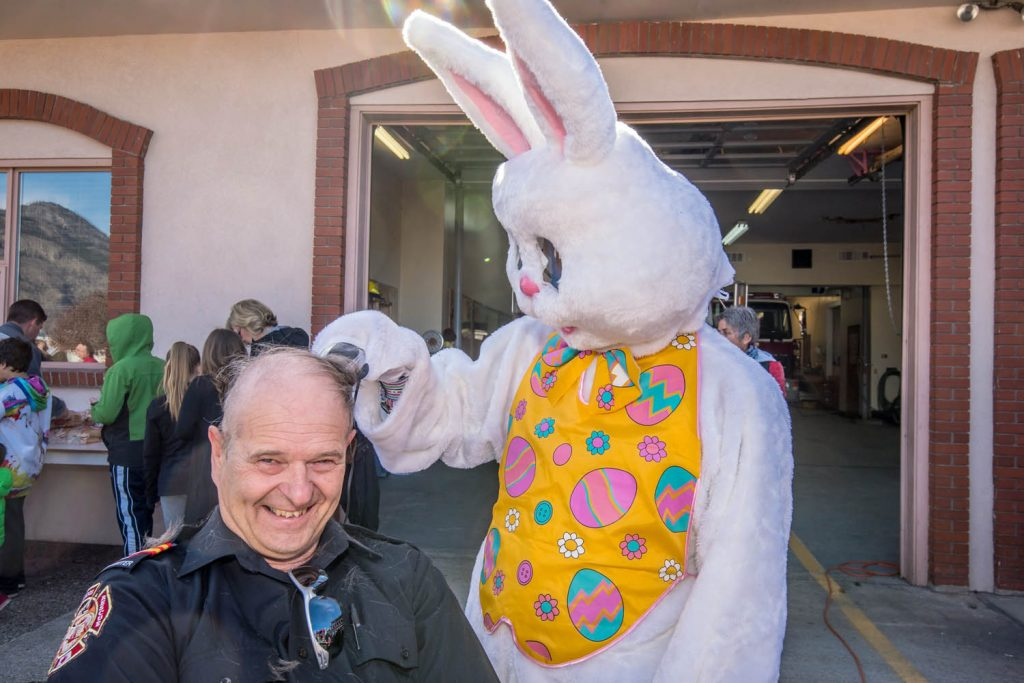 """The Easter Bunny, aka Ken Baker of the Osoyoos Times, gives firefighter Colin Lancaster a """"hare cut."""" The Osoyoos firefighters were getting their heads shaved and selling hot dogs to raise money for the Canadian Cancer Society during Easter Eggstravaganza last March. (Richard McGuire photo)"""