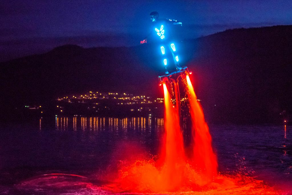 Curtis Pangrass flew and flipped through the air propelled by powerful jets of water in the sport of flyboarding. For this demonstration in May, he wore a suit with lights and the water jets were lit up with brilliant red lights. A member of Team Canfly, Pangrass, from Edmonton, did demonstrations at Walnut Beach Resort. The event was arranged by Travis Blacklin, proprietor of Canadian Jet Pack Adventures, who was operating a flyboarding concession at the resort again this summer. (Richard McGuire photo)