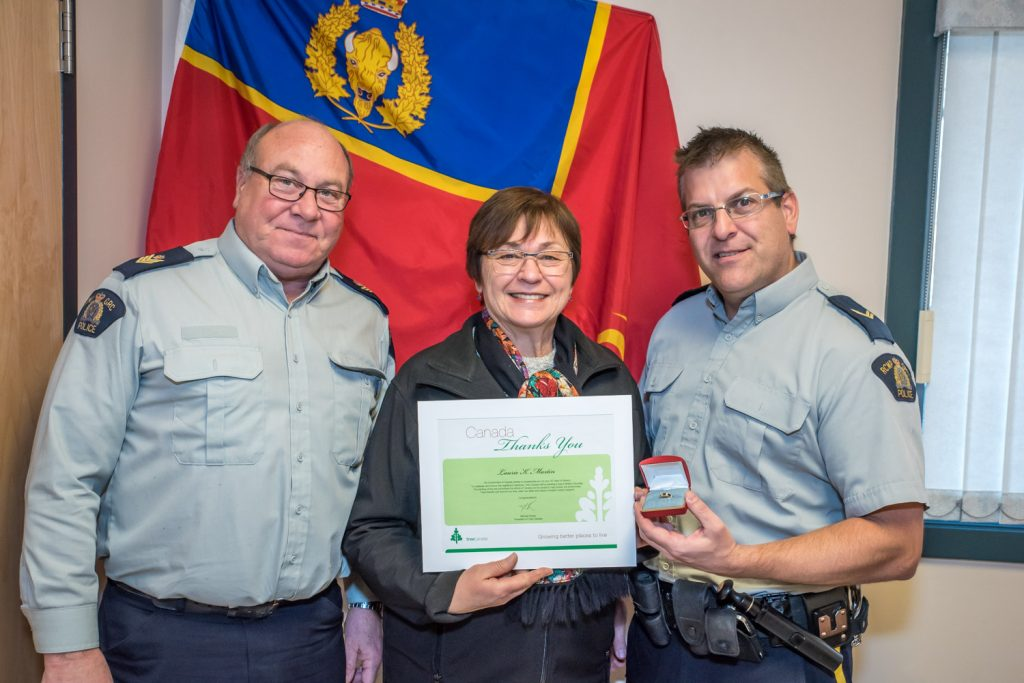 Laurie Martin retired recently after 30 years as a federal public servant and 37 years in administration with the RCMP. She has worked with Osoyoos RCMP for 17 years. Congratulating her are Osoyoos Detachment Commanding Officer Sgt. Randall Bosch (left) and Cpt. Jason Bayda. Martin received a certificate and a ring and a tree is being planted in her honour. (Richard McGuire photo)